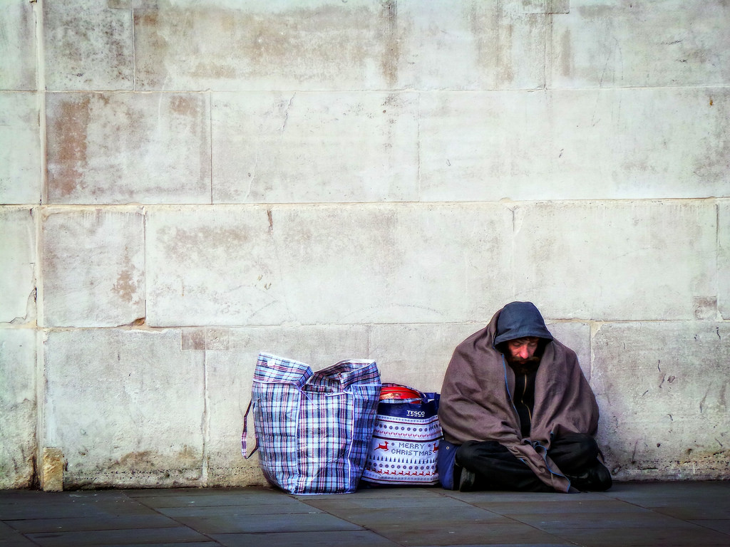 homeless man seated on ground